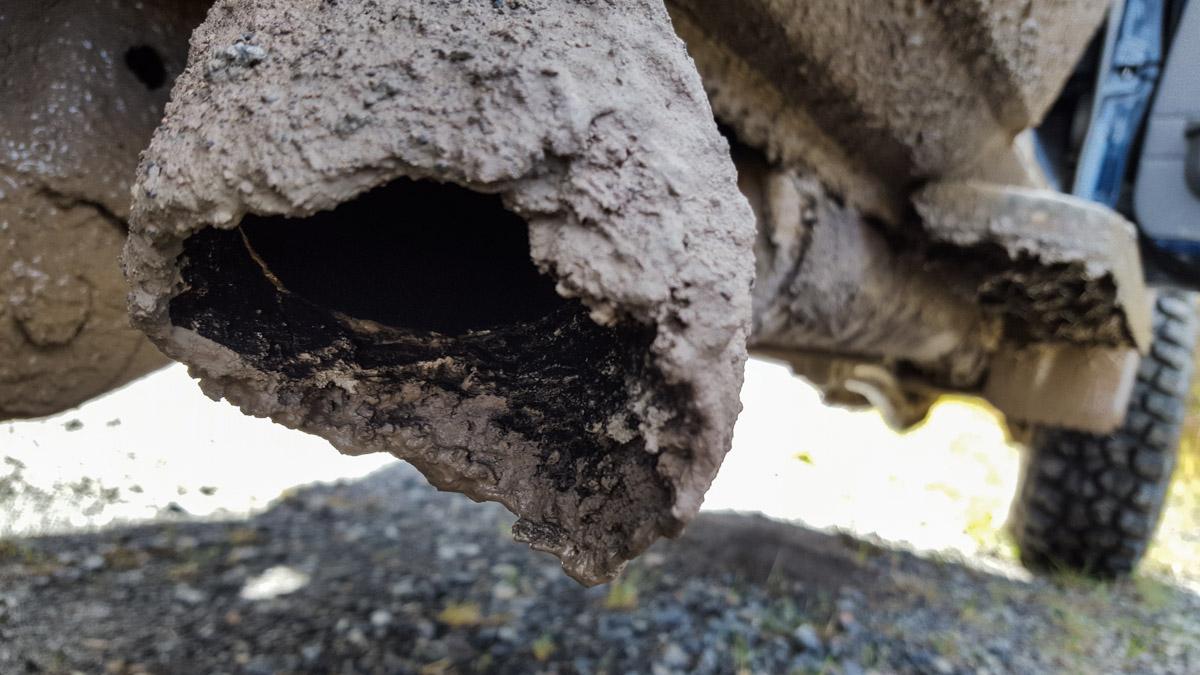 Der Auspuff versteckt sich unter einer dicken Dreckschicht.